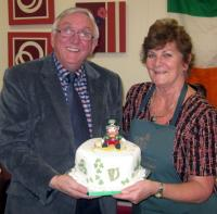 Roger Cressey is presented with his cake by Suzanne Brindley